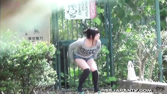 Girl hiding in the bushes and pissing